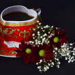 Cup of coffee and flowers on a black   background — Stock Photo
