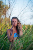 Portrait of a beautiful young girl in high grass — Stock Photo