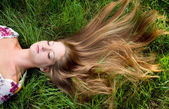 Young beautiful girl lie in grass — Stock Photo