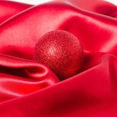 Christmas ball on silk — Stock Photo