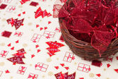 Red christmas bows in wicker basket — Stok fotoğraf