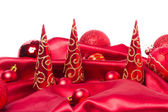 Red christmas balls and xmas trees on red cloth — Stok fotoğraf