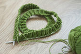 Heart shape knitting needles, and green wool yarn - top view — Stock Photo