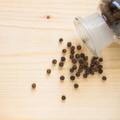 Black pepper (Piper nigrum) on the wooden table — Stock Photo