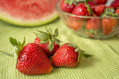 Three strawberries in Huelva on a green tablecloth. — Stock Photo