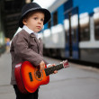 Boy with a guitar on a railway station — Stock Photo #32432471