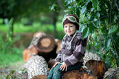 Portrait of a boy, sitting on a tree trunk — Stock Photo