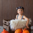 Stock Photo: Boy with hat and suspenders in a wooden tray