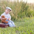 Boy with a teddy bear, sitting on suitcase — Stock Photo