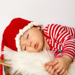 Stock Photo: Little baby boy, dressed in santa clothes, sleeping on a sledge