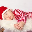 Little baby boy, dressed in santa clothes, sleeping on a sledge — Stock Photo