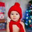 Little boy with red hat and scarf in front of a christmas tree — Stock Photo