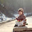 Little boy with a picnic basket on a railway station — Stock Photo #32467185
