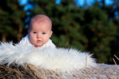 Baby boy, lying on a haystack — Stock Photo