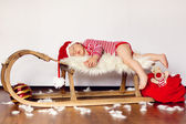 Little baby boy, dressed in santa clothes, sleeping on a sledge — Stockfoto