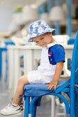 Boy sitting on a chair in a resataurant — Stock Photo