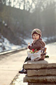 Little boy with a picnic basket on a railway station — Stok fotoğraf