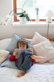 Boy, lying on the bed the bed, playing with tablet — Stockfoto