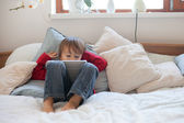 Boy, lying on the bed the bed, playing with tablet — Stock Photo