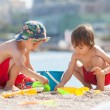 Two cute kids, playing in the sand on the beach — Stock Photo #49313935