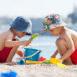 Two cute kids, playing in the sand on the beach — Stock Photo #49313961