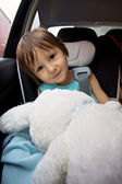 Adorable baby boy in safety car seat, holding teddy rabbit — Stock fotografie