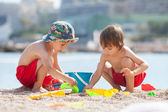 Two cute kids, playing in the sand on the beach — Stock Photo