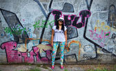 Smiling Girl with Wall Covered with Graffiti Behind — Stock Photo
