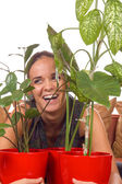 Woman laughs between plants — Stock Photo