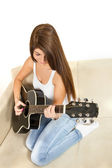 Girl playing guitar on the couch — Foto de Stock