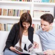 Happy couple at home reading newspapers in front of library — Stock Photo