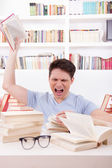 Angry student surrounded by books throws a book — Zdjęcie stockowe