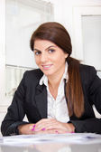Business woman with ponytail sitting in office — Stock fotografie