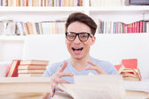 Happy student surrounded by books — Stockfoto