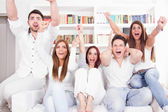 Cheerful friends watching football game on tv — Stock Photo