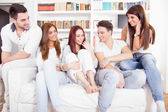 Friends having conversation on sofa at home — Stock Photo