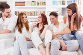 Group of friends sitting on sofa talking and smiling — Stock Photo