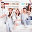 Group of friends watching bad game on tv with expression — Stock Photo