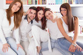 Group of friends smiling and sitting together on sofa at home — Stock Photo