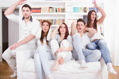 Group of friends watching bad game on tv with expression — Photo