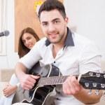 Man in white shirt playing guitar and singing — Stock Photo