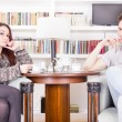 Serious couple sitting on armchairs in the library — Stock Photo