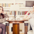 Serious glamor couple sitting on armchairs in the library — Stock Photo