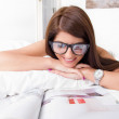 Young woman reading papers lying on the bed — Stock Photo #41067735