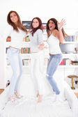 Happy party girls jumping on couch — Stock Photo