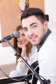 Man playing guitar and singing to a cute girl — Stock Photo