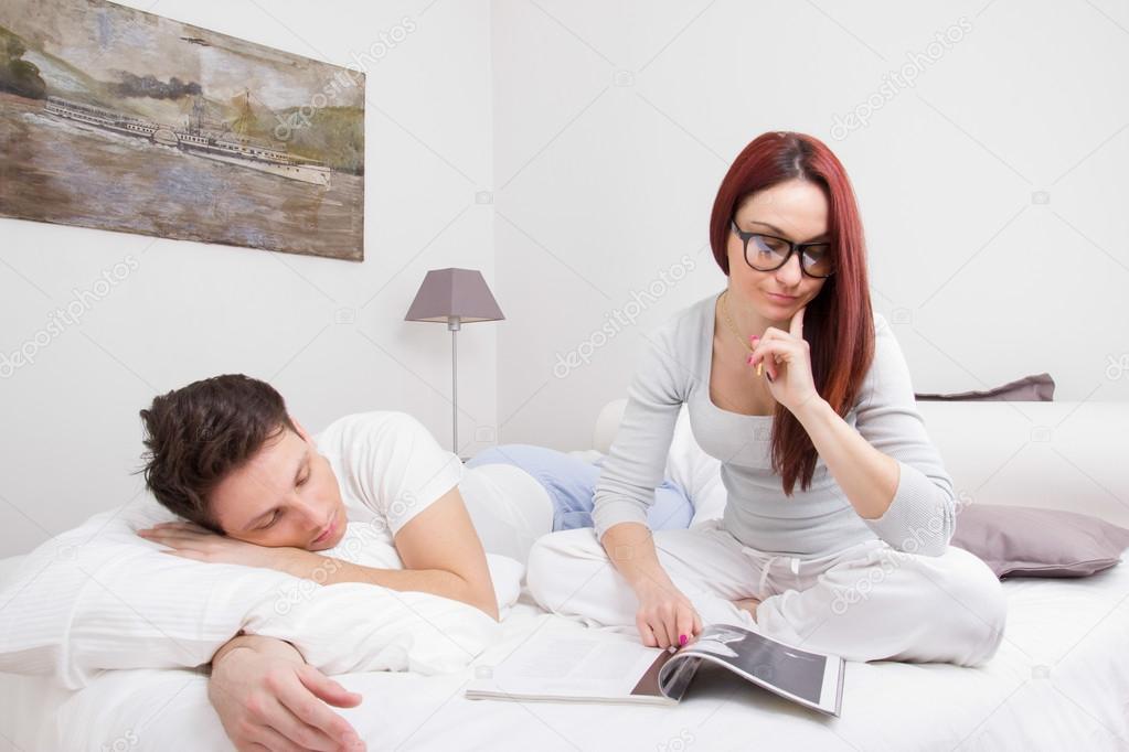 libro de lectura de la mujer en la cama y hombre durmiendo al lado de ella foto de stock. Black Bedroom Furniture Sets. Home Design Ideas