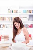 Beautiful librarian girl reading books — Stockfoto