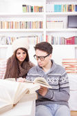 Happy couple reading books at home — Stock Photo