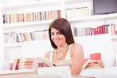 Woman studying and reading books and smiling — Stock Photo